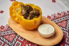 Παραδοσιακό ρουμανικό ή μολδαβικό γεύμα sarmale με το κρέας, το ρύζι και τα λαχανικά στο πιπέρι belle με το souce στο ξύλινο πιάτ στοκ φωτογραφία με δικαίωμα ελεύθερης χρήσης