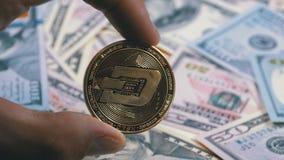 Παραδώστε τα δάχτυλα κρατά μια χρυσή εξόρμηση νομισμάτων σε ένα υπόβαθρο με Bill των δολαρίων φιλμ μικρού μήκους