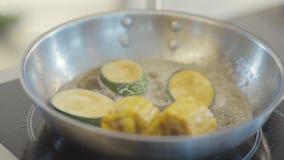 Παραδώστε τα μαύρα τεθειμένα γάντια κολοκύθια και το καλαμπόκι λατέξ καυτό παν στενό σε επάνω τηγανίσματος απόθεμα βίντεο