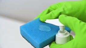 Παραδώστε τον πράσινο διανομέα ώθησης γαντιών και το υγρό απορρυπαντικό που συμπιέζονται στο μπλε σφουγγάρι απόθεμα βίντεο