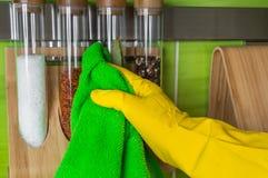 Παραδώστε το γάντι με το πράσινο κουρέλι σκουπίζει τα μπουκάλια καρυκευμάτων Στοκ Εικόνα