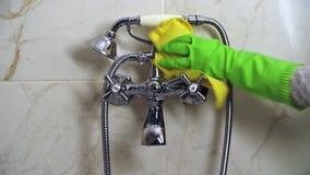 Παραδώστε το πράσινο γάντι καθαρίζει τη στρόφιγγα λουτρών με το κίτρινο κουρέλι απόθεμα βίντεο