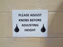 Παρακαλώ ρυθμίστε τα εξογκώματα πρίν ρυθμίζει το σημάδι ύψους με τον εγκιβωτισμό της τσάντας στον τοίχο στοκ φωτογραφίες με δικαίωμα ελεύθερης χρήσης
