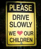 Παρακαλώ οδηγήστε αργά εμείς αγαπά το σημάδι παιδιών μας Στοκ εικόνες με δικαίωμα ελεύθερης χρήσης