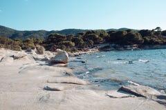 Παραλία θάλασσας με το λοφώδες τοπίο στον ηλιόλουστο μπλε ουρανό Πετρώδης παραλία με το μπλε νερό και τα πράσινα δέντρα Θερινές δ Στοκ Φωτογραφίες