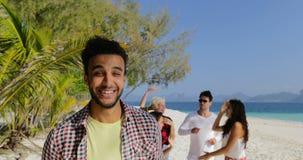 Παραλία, ισπανικά νέα γυαλιά ήλιων χαμόγελου τύπων ευτυχή απογειωμένος, εύθυμος άνδρας και χορεύοντας φίλοι γυναικών μαζί επάνω απόθεμα βίντεο