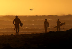 παραλία κάτω από το περπάτημα surfers ηλιοβασιλέματος στοκ εικόνες
