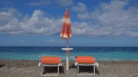 Παραλία με τα deckchairs και sunshade απόθεμα βίντεο