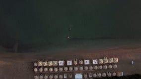 Παραλία με τα sunbeds και τους ανθρώπους που κολυμπούν στην ακτή, εναέρια φιλμ μικρού μήκους