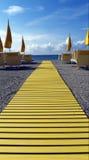 Παραλία με τις κίτρινες ομπρέλες και την έδρα Στοκ φωτογραφία με δικαίωμα ελεύθερης χρήσης