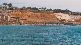 Παραλία με τις ομπρέλες και Sunbeds στο ξενοδοχείο πολυτελείας στη Ερυθρά Θάλασσα κοντά στην κοραλλιογενή ύφαλο Αίγυπτος φιλμ μικρού μήκους