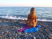παραλία που κάθεται τις πετρώδεις νεολαίες γυναικών Στοκ Εικόνα