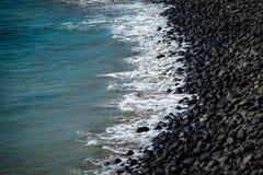 Παραλία των μαύρων ηφαιστειακών βράχων στη γραμμή ακτών στοκ φωτογραφίες