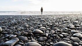 Παραλία χαλικιών με ένα θολωμένο πρόσωπο που στέκεται στο υπόβαθρο στοκ εικόνα
