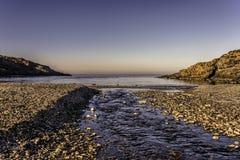 Παραλία χαλικιών με ένα ρεύμα του νερού που ρέει σε μια ακίνητη θάλασσα κάτω από τους μπλε ουρανούς Στοκ φωτογραφία με δικαίωμα ελεύθερης χρήσης