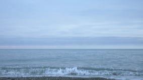 Παραλία χαλικιών στο ηλιοβασίλεμα Τα κύματα splatter και σπάσιμο στα σταγονίδια r φιλμ μικρού μήκους