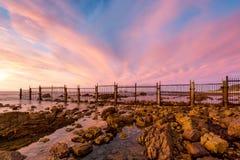 Παραλία Osullivan στο ηλιοβασίλεμα έπειτα η παλαιά γραμμή φρακτών εγκαταστάσεων καθαρισμού Στοκ Εικόνες