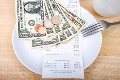 Παραλαβή υπολογισμού Gratuity στο πιάτο με τα χρήματα στοκ εικόνες