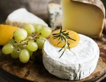 Παραλλαγή του τυριού και των πράσινων σταφυλιών σε μια ξύλινη ιδέα συνταγής φωτογραφίας τροφίμων πιατελών στοκ εικόνα με δικαίωμα ελεύθερης χρήσης