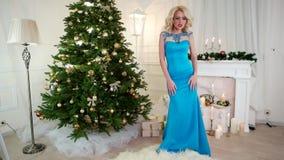 Παραμονή Πρωτοχρονιάς, κόμμα, το όμορφο κορίτσι στο εορταστικό φόρεμα χορεύει κοντά στο χριστουγεννιάτικο δέντρο στις διακοπές Χρ φιλμ μικρού μήκους