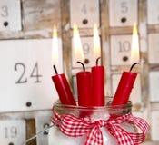 Παραμονή Χριστουγέννων: τέσσερα κόκκινα καίγοντας κεριά με ένα shabby άσπρο adve στοκ εικόνες με δικαίωμα ελεύθερης χρήσης