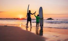Παραμονή surfers πατέρων και γιων στην παραλία ηλιοβασιλέματος στοκ φωτογραφία