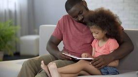 Παραμύθια ανάγνωσης πατέρων φροντίδας μεγαλοφώνως στη μικρή κόρη του, οικογενειακή αγάπη στοκ φωτογραφίες με δικαίωμα ελεύθερης χρήσης