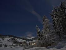 Παραμύθι χειμερινής νύχτας πανσελήνων, βουνά και ένα χωριό στην απόσταση στοκ εικόνες με δικαίωμα ελεύθερης χρήσης