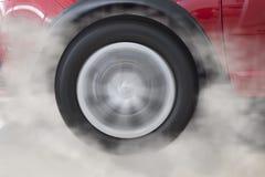 παρασύρουσα και καπνίζοντας ρόδα του νέου κόκκινου αυτοκινήτου Στοκ φωτογραφία με δικαίωμα ελεύθερης χρήσης