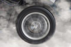 παρασύρουσα και καπνίζοντας ρόδα του νέου μαύρου αυτοκινήτου Στοκ Εικόνες