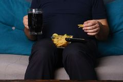 Παρατρώγοντας, στατικός τρόπος ζωής, εθισμός τροφίμων στοκ εικόνες