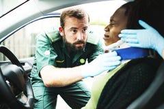 Παραϊατρικός τοποθετώντας ένα αυχενικό περιλαίμιο σε μια τραυματισμένη γυναίκα από το τροχαίο στοκ εικόνα με δικαίωμα ελεύθερης χρήσης