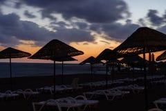 Παραλία θάλασσας με τις ομπρέλες και sunbeds στο ηλιοβασίλεμα στοκ εικόνες