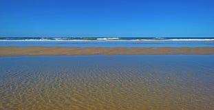 Παραλία και θάλασσα κάτω από έναν μπλε ουρανό Στοκ Φωτογραφία
