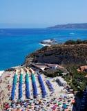 Παραλία με τις ζωηρόχρωμες ομπρέλες και τη θάλασσα Tropea στην Καλαβρία (Ιταλία) Στοκ Φωτογραφίες