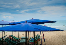 Παραλία με τις καρέκλες γεφυρών και τις ομπρέλες παραλιών μια ηλιόλουστη ημέρα Στοκ Φωτογραφία