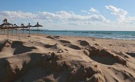 Παραλία με τις ομπρέλες και τη θάλασσα Στοκ Φωτογραφίες
