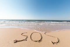 Παραλία με το SOS λέξης άμμου Στοκ Φωτογραφία