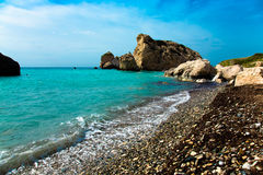 Παραλία χαλικιών και μπλε θάλασσα στον τόπο γεννήσεως Aphrodites Πάφος, Στοκ Φωτογραφία