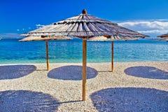 Παραλία χαλικιών και τυρκουάζ ομπρέλα θάλασσας στοκ εικόνες