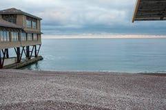 Παραλία χαλικιών με ένα σπίτι στην αποβάθρα στο ηλιοβασίλεμα Στοκ Εικόνες