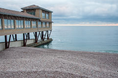 Παραλία χαλικιών με ένα σπίτι στην αποβάθρα στο ηλιοβασίλεμα Στοκ Φωτογραφίες