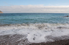 Παραλία χαλικιών μια ηλιόλουστη ημέρα Στοκ Εικόνες