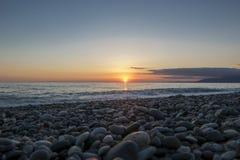 Παραλία χαλικιών στο όμορφο ηλιοβασίλεμα Στοκ Φωτογραφία