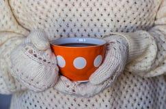 Παραδίδει τα πλεκτά γάντια κρατώντας ένα φλυτζάνι του coffe Στοκ Εικόνες