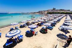 παραλιών ακτών θερινή κυματωγή πετρών άμμου της Κύπρου μεσογειακή Ομπρέλες παραλιών κλίση που αλιεύει το μεσογειακό καθαρό τόνο θ Στοκ Εικόνες