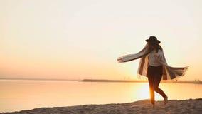 παραλιών ξένοιαστη γυναίκα ζωτικότητας διακοπών ηλιοβασιλέματος έννοιας χορεύοντας υγιής ζωντανή φιλμ μικρού μήκους
