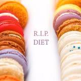Παραδοσιακά γαλλικά ζωηρόχρωμα macaroons σειρές σε ένα κιβώτιο με τις λέξεις ΣΧΙΖΟΥΝ τη διατροφή Στοκ Φωτογραφίες