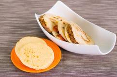 Παραδοσιακά εύγευστα arepas, τεμαχισμένο τυρί αβοκάντο κοτόπουλου και τυριού Cheddar και τεμαχισμένο βόειο κρέας στο ξύλινο υπόβα Στοκ Εικόνες