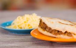 Παραδοσιακά εύγευστα arepas, τεμαχισμένο τυρί αβοκάντο κοτόπουλου και τυριού Cheddar και τεμαχισμένο βόειο κρέας στο ξύλινο black Στοκ εικόνα με δικαίωμα ελεύθερης χρήσης